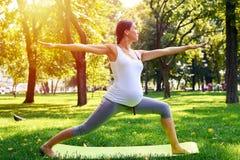 Den harmoniska gravida kvinnan som mediterar i yoga, poserar utomhus Arkivfoto