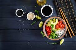 Den hawaianska laxfisken petar bunken med ris, avokadot, paprika, sesamfrö och limefrukt arkivbilder