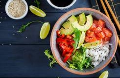 Den hawaianska laxfisken petar bunken med ris, avokadot, paprika, sesamfrö och limefrukt royaltyfri fotografi