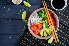 Den hawaianska laxfisken petar bunken med ris, gurkan, rädisan, sesamfrö och limefrukt royaltyfri fotografi