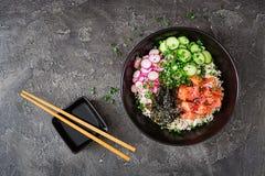 Den hawaianska laxfisken petar bunken med ris, rädisan, gurkan, tomaten, sesamfrö och havsväxter royaltyfri foto