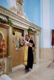 Den heliga fadern döper det nyfödda barnet Royaltyfria Bilder