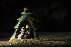 Den heliga familjen i en lantlig julkrubba arkivbilder
