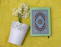 Den heliga quran- och påskliljabuketten på det gula hantverket skyler över brister backgroun Royaltyfri Bild