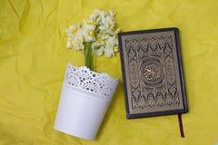 Den heliga quran- och påskliljabuketten på det gula hantverket skyler över brister bakgrund Royaltyfri Bild