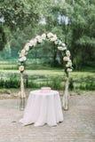 Den hellånga sikten av bågen med vita blommor som förläggas bak tabellen med små rosa färger, boxas på den Royaltyfri Fotografi