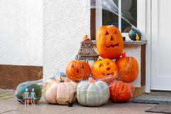 Den hem- dörren dekorerade för halloween med den läskiga stålar-nolla-lyktan pumpen Arkivbilder