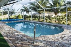 Den hem- härliga simbassängen med blått vatten och gömma i handflatan Royaltyfri Fotografi
