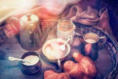 Den hem- lantliga mycket hemtrevliga frukosten i morgonsolen med tappningkaffeuppsättningen, mjölkar, driftstopp och giffel, stil Royaltyfri Fotografi