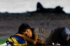 Den hemlösa flickan lägger på hennes ryggsäck på gatan av Singapore royaltyfri fotografi