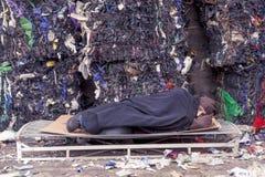 Den hemlösa mannen sover i avfallsen Royaltyfria Bilder