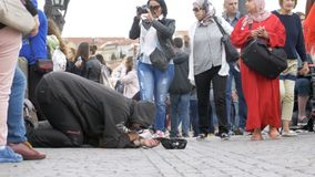 Den hemlösa tiggaren Man med en hatt på trottoaren tigger för allmosa från att förbigå för folk lager videofilmer