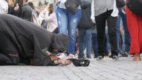 Den hemlösa tiggaren Man med en hatt på trottoaren tigger för allmosa från att förbigå för folk stock video