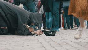 Den hemlösa tiggaren Man med en hatt på trottoaren tigger för allmosa från att förbigå för folk arkivfilmer