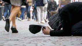 Den hemlösa tiggaren Man med en hatt på trottoaren tigger för allmosa från att förbigå för folk långsam rörelse stock video