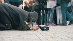 Den hemlösa tiggaren Man med en hatt på trottoaren tigger för allmosa från att förbigå för folk långsam rörelse lager videofilmer