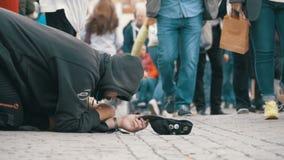 Den hemlösa tiggaren Man med en hatt på trottoaren tigger för allmosa från att förbigå för folk långsam rörelse arkivfilmer