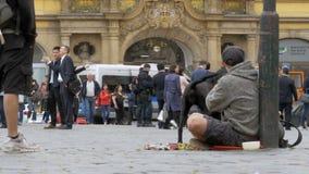 Den hemlösa tiggaren Man med en hund på trottoaren tigger för allmosa från att förbigå för folk lager videofilmer
