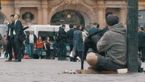 Den hemlösa tiggaren Man med en hund på trottoaren tigger för allmosa från att förbigå för folk stock video