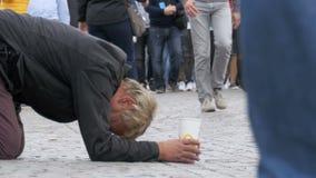 Den hemlösa tiggaren Man med den plast- koppen i hans händer på trottoaren tigger för allmosa från att förbigå för folk lager videofilmer
