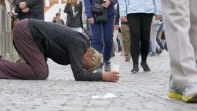 Den hemlösa tiggaren Man med den plast- koppen i hans händer på trottoaren tigger för allmosa från att förbigå för folk stock video