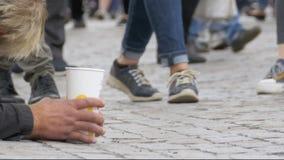 Den hemlösa tiggaren Man med den plast- koppen i hans händer på trottoaren tigger för allmosa från att förbigå för folk arkivfilmer