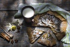 Den hemlagade äppelpajen med pudrat socker, kryddor och mjölkar, tjänat som med en textilhandduk på ett träbräde, bakgrund överka Royaltyfria Foton