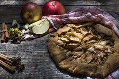 Den hemlagade äppelpajen med pudrat socker, kryddor tjänade som med en textilhandduk på ett träbräde, bakgrund Top beskådar Royaltyfri Fotografi