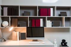 Den hemlagade arbetsplatsen, en dator står på en tabell, är en skrivbordlampa glänsande på bakgrunden av en hylla med böcker och  arkivfoto
