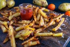Den hemlagade bakade potatisen steker med ketchup på trätillbaka jordning royaltyfri bild