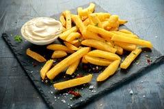 Den hemlagade bakade potatisen steker med majonnäs som är salt, peppar på svart stenbräde Royaltyfri Fotografi