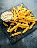 Den hemlagade bakade potatisen steker med majonnäs som är salt, peppar på svart stenbräde Arkivbild