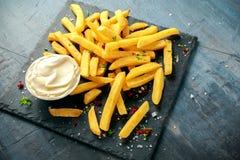 Den hemlagade bakade potatisen steker med majonnäs som är salt, peppar på svart stenbräde Royaltyfria Bilder