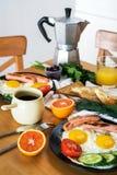 Den hemlagade frukosten med stekte ägg rostar korvfruktgrönsaker orange fruktsaft och kaffe Arkivbild