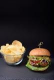 Den hemlagade hamburgaren med frasiga potatischiper kritiserar på brädet över svart bakgrund utrymme för fri text Royaltyfria Bilder