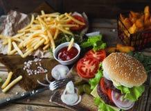 Den hemlagade hamburgaren, stekte potatisar, fransman steker, snabbmatuppsättningen Arkivbild