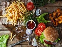 Den hemlagade hamburgaren, stekte potatisar, fransman steker, snabbmatuppsättningen Arkivbilder