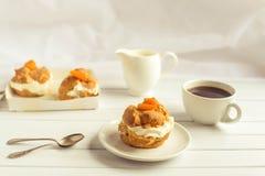 Den hemlagade nya kräm- puffen med piskade kräm och aprikors, kopp kaffe och mjölkar tillbringaren Arkivbild
