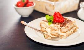 Den hemlagade tiramisukakan dekorerade med italiensk kokkonst för jordgubbar, selektiv fokus arkivfoto