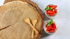 Den hemlagade utsökta efterrätttiramisuen i exponeringsglas dekorerade med jordgubben, mintkaramell, på en trästubbe Autentisk li royaltyfri fotografi