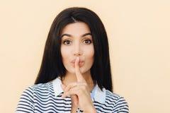 Den hemliga kvinnlign gör för att hyssja tecknet, skvallrar med bästa vän, uppehällepekfinger på kanter, har långt mörkt hår, pos arkivbilder