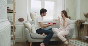 Den hemtrevliga atmosfärlägenheten, paret som firar dagen för valentin s, man för att ge till hans flickvän en närvarande röd ask stock video