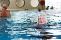 Den höga aktiva damen simmar i pölen Arkivbild