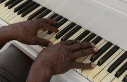 Den höga mannen spelar pianot Arkivbilder