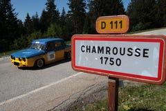Den historiska tävlings- bilen och ingången undertecknar in byn Royaltyfria Bilder