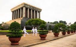 Den Ho Chi Minh mausoleet med den vita likformign tjäna som soldat att marschera framme som patrullerar området royaltyfri foto