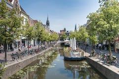Den holländska stadsdelftfajans med kanalcyklar och folk royaltyfri bild