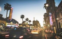 Den Hollywood boulevarden på solnedgångskymning med suddiga bilar tänder spårar - gå av berömmelse arkivbild