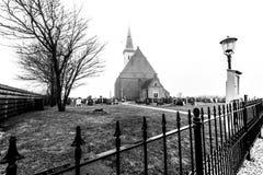 Den Hoorn, los Países Bajos - 25 de febrero de 2010: Mañana de niebla del otoño, cementerio delante de la iglesia de Den Hoorn en imagen de archivo