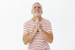 Den hoppfulla gamala mannen i behov och problem som bär den randiga t-skjortan med det gråa skägget som rymmer händer ber in, att royaltyfri foto